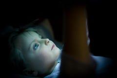 Flicka för litet barn som hemma använder minnestavlateknologi i säng vid natt Allvarlig eller toughtful ungedotter, i att hålla ö Royaltyfri Bild