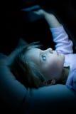 Flicka för litet barn som hemma använder minnestavlateknologi i säng vid natt Allvarlig eller toughtful ungedotter, i att hålla ö Royaltyfri Foto