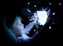 Flicka för litet barn som hemma använder minnestavlateknologi i säng vid natt förvånad ungedotter i hållande ögonen på film för s royaltyfria bilder