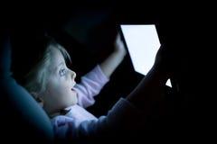 Flicka för litet barn som hemma använder minnestavlateknologi i säng vid natt Lycklig förvånad ungedotter, i att hålla ögonen på  Arkivfoto
