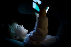 Flicka för litet barn som hemma använder minnestavlateknologi i säng vid natt Lycklig ungedotter i hållande ögonen på film för so Royaltyfria Foton