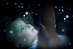 Flicka för litet barn som hemma använder minnestavlateknologi i säng vid natt toughtful ungedotter i hållande ögonen på film för  Arkivbild
