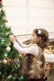 Flicka för litet barn som hemma dekorerar julgranen med bollar, inomhus close upp Julfilial och klockor arkivbilder