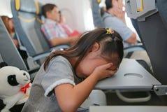 Flicka för litet barn som sover på tabellen av flygplanet arkivfoton