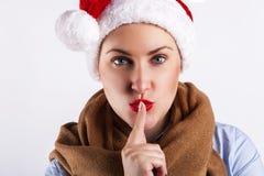 Flicka för lycklig jul i Santa Hat som gör ett hyssjatecken Fotografering för Bildbyråer