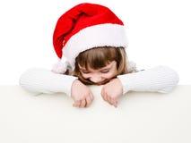 Flicka för lycklig jul med den santa hatten bak det vita brädet som ser D Royaltyfria Bilder