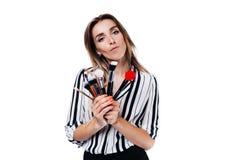 Flicka för makeupkonstnär på en vit bakgrund med borstar royaltyfri foto