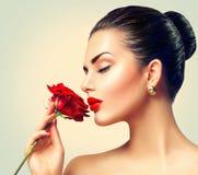 Flicka för modebrunettmodell med den röda rosen Arkivfoton