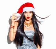 Flicka för modell för skönhetjulmode med långt hår i den röda santa hatten royaltyfria foton