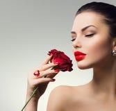 Flicka för modemodell med den röda rosen i hennes hand Arkivbilder
