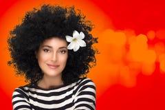 Flicka för skönhetmodebrunett med blomman i lockig afro- frisyr Royaltyfria Bilder