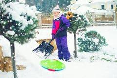 Flicka för skolaålder som arbetar med skyffeln i snöig gård för vinter Royaltyfri Foto