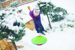 Flicka för skolaålder som arbetar med skyffeln i snöig gård för vinter Arkivfoto