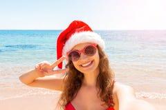 Flicka för sommarstrandsemester i den santa hatten som tar det roliga mobila selfiefotoet med smartphonen Flicka som bär röd solg arkivbild
