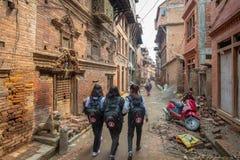 Flicka för tre skola som går ner en smal gata arkivfoton