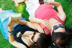 Flicka för två asiat som ligger på ett gräs Royaltyfri Fotografi