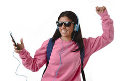 Flicka för ung kvinna eller studentmed mobiltelefonen som lyssnar till musikhörlurar som sjunger och dansar Fotografering för Bildbyråer