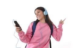 Flicka för ung kvinna eller studentmed mobiltelefonen som lyssnar till musikhörlurar som sjunger och dansar Arkivbild