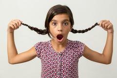 Flicka förvånad flätad tråd för innehav Royaltyfri Foto