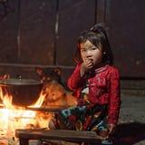 Flicka från svart Hmong stamsammanträde vid brand Royaltyfri Bild