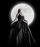 Flicka för mörkernattMoon med den svart klänningen Arkivbilder