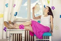 Flicka framme av fönsterholdingventilatoren Royaltyfri Bild