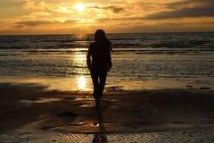 Flicka framme av havssolnedgången Arkivfoto