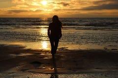 Flicka framme av havssolnedgången Fotografering för Bildbyråer