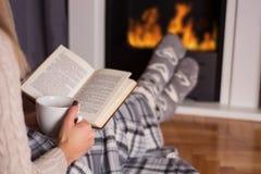 Flicka framme av läsebok- och värmefoten för spis på brand arkivbilder