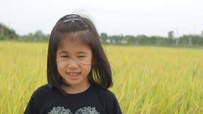Flicka framme av risfältet Arkivfoto