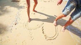 Flicka Guy Feet Barefoot Draw Heart på sandstranden på vågkanten stock video