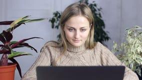 Flicka hemma som sitter och arbetar på en bärbar dator lager videofilmer