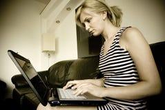 flicka henne bärbar datorworking Arkivbild