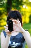 flicka henne mobilt telefonfoto som tar genom att använda Arkivfoto