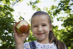 Flicka hållande halva åt Apple utomhus Arkivfoto