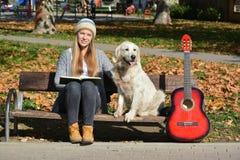 Flicka, hund, bok och gitarr på en bänk Royaltyfri Foto