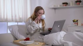 Flicka i ?mbetsdr?kt som dricker kaffe i s?ng och arbetar p? b?rbara datorn, frilans- begrepp arkivfilmer