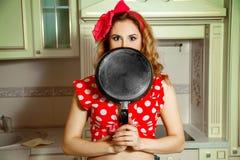 Flicka i övre stil för stift som poserar i köket med stekpannan i mummel Arkivfoton