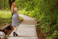 Flicka i affärsklänning som går i trädgården Arkivbilder