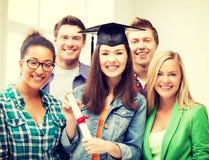 Flicka i avläggande av examenlock med certifikatet Arkivfoton