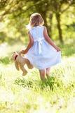 Flicka i bärande nallebjörn för fält Royaltyfria Bilder