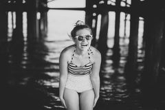 Flicka i baddräkt under pir arkivfoton