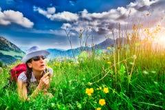 Flicka i bergäng som blåser blomman fotografering för bildbyråer