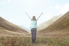Flicka i bergen en sikt från baksidan med lyftta armar royaltyfri foto