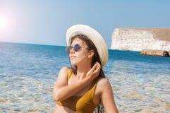 Flicka i bikini, exponeringsglas och hatt i klart havsvatten Fotografering för Bildbyråer