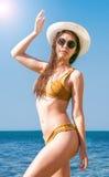 Flicka i bikini, exponeringsglas och hatt i klart havsvatten Royaltyfri Foto