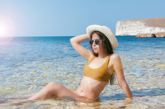 Flicka i bikini, exponeringsglas och hatt i klart havsvatten Royaltyfria Bilder