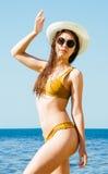Flicka i bikini, exponeringsglas och hatt i klart havsvatten Arkivbild