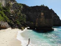 Flicka i bikini som g?r p? stranden n?ra havet Semester i Nusa Penida Foto fr?n surret royaltyfri foto