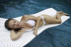 Flicka i bikinin som flottörhus på en raft arkivfoto